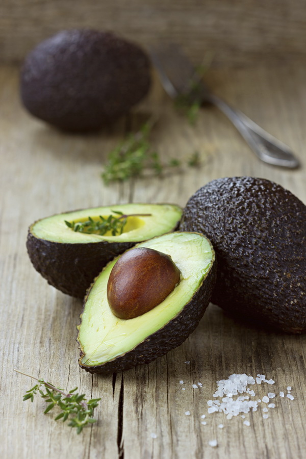Avocado half with herb thyme on a wooden rustic board